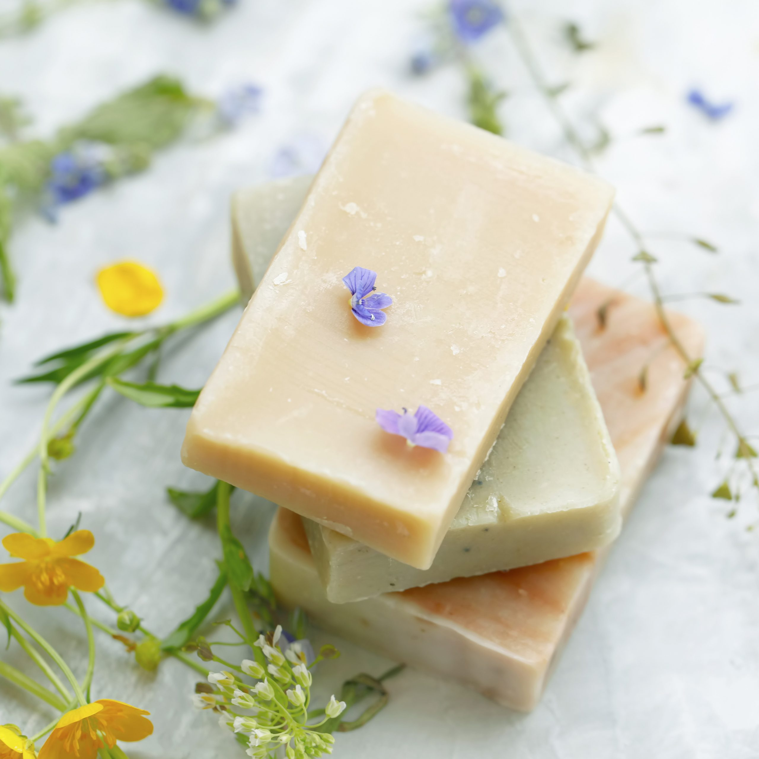 Natural handmade soap bars with organic medicinal plants and flowers.Homemade beauty products with natural essential oils from plants and flowers, top view closeup photo